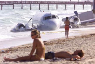 on beach with wrecked plane